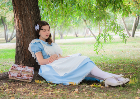 Girl pupil in the image of a character from a fairy tale fell sleep under a tree with a book. Stock Photo