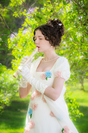 Portrait girl musician in a beautiful white dress decorated flowers with a flute in a sunny summer day outdoors.