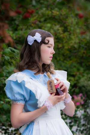 girl in the image of fairy tale heroine drinks the drink of glass bottle cherry color with a label drink me. Stock Photo