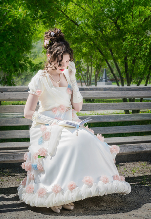 young woman in a smart long white dress is reading a love story on a park bench and is enjoying her.