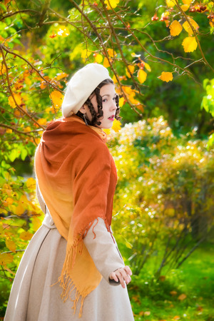 Girl with a surprised look in her coat and take on a walk in the autumn afternoon, view from the back. 写真素材