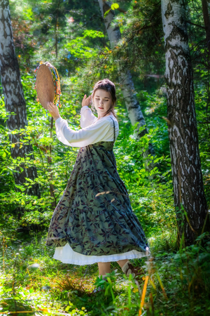 Young woman of a sorceress performs a ritual dance with a tambourine in the forest on a summer sunny day.