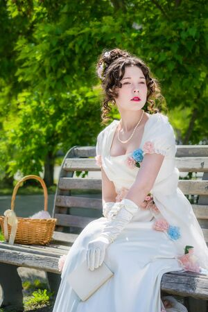 Portrait of a young bride girl in a historical white dress with a book in hands outdoors in a park on a bench