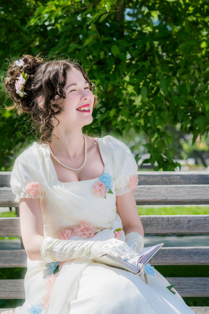 Young happy girl in a long white bride dress with a smile is reading book about love story on a park bench.