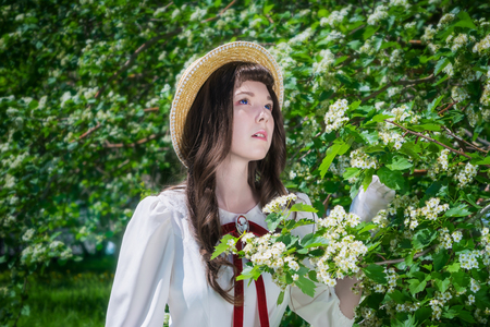 Portrait charming girl in white dress and straw hat near blooming hawthorn bush in park 免版税图像