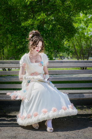 young girl in a smart long white dress is reading a love story on a park bench and is enjoying her.