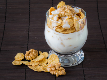 Yogurt with cornflakes and walnuts in a glass goblet on a bamboo napkin.