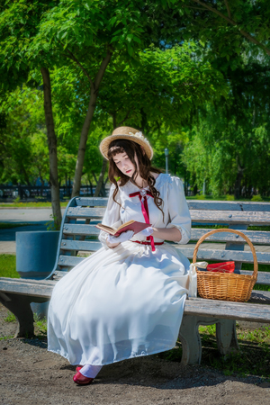 Young girl in a smart long white dress is reading book a love story on a park bench. Stock Photo