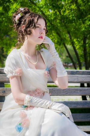 Portrait d'une jeune mariée femme vêtue d'une robe blanche historique avec un livre en mains à l'extérieur dans un parc sur un banc. Banque d'images