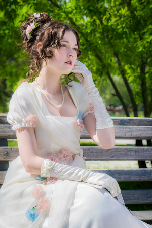 Portrait of a young bride woman in a historical white dress with a book in hands outdoors in a park on a bench.