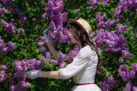 Girl in a white dress and straw hat hugs a flowering lilac in the park.