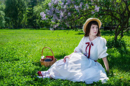 Girl in a white dress and straw hat on a sunny spring day is resting, sitting under a tree of blossoming lilacs.