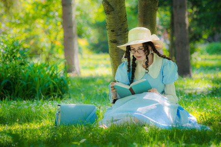 Girl in the image of a character from a fairy tale is sitting under a tree with a reading book. Banco de Imagens - 122285193