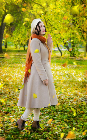 Girl in a light coat and beret in the autumn day on a walk in the park during the fall leaf looks at the falling leaves.