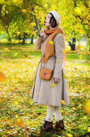 Woman in a light coat and beret in the autumn day on a walk in the park during the fall leaf looks at the falling leaves.