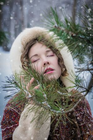 Portrait of a girl in a fur coat standing near a conifer tree and enjoying a beautiful winter day, her eyes closed from pleasure. Reklamní fotografie