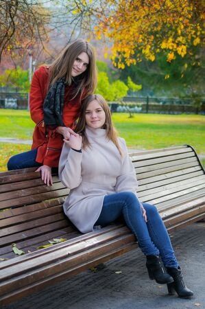 Two beautiful girlfriends on a sunny autumn day sitting side by side on a bench and are laughing.