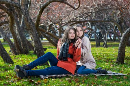 Two pretty girlfriends are sitting on the lawn in the park on a warm sunny autumn day.