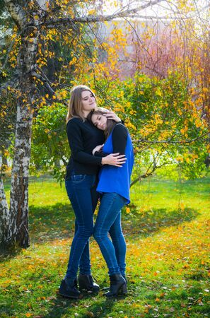 Two pretty girlfriends are hugging in the autumn park on a sunny day and smiling.