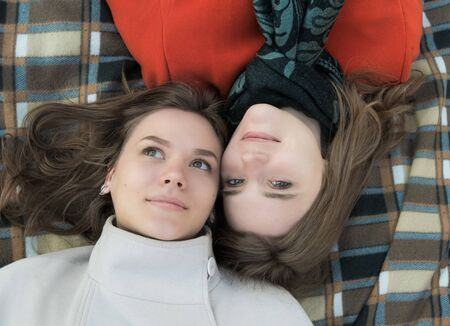 Portrait of two beautiful happy girlfriends who are lying on a plaid, top view. Stockfoto - 132092528