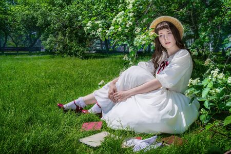 Nice girl in a white dress sits on a lawn in a park under a bush of a flowering hawthorn.