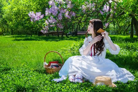 Nice girl in a white dress sits on a lawn in a park under a bush of blooming lilacs and combes her long hair.