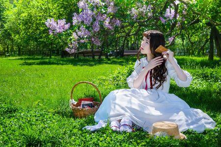 Jolie fille en robe blanche est assise sur une pelouse dans un parc sous un buisson de lilas en fleurs et peigne ses longs cheveux.