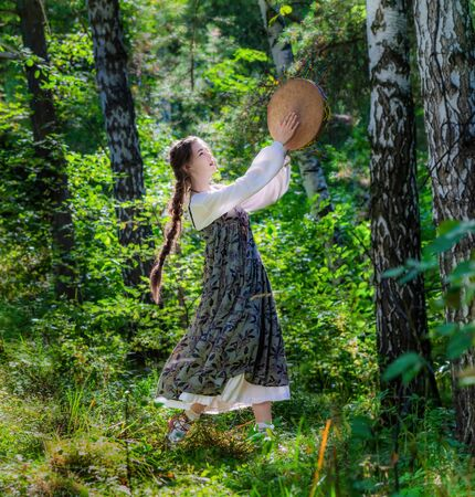 Young girl witch performs a ritual dance with a tambourine in the forest.