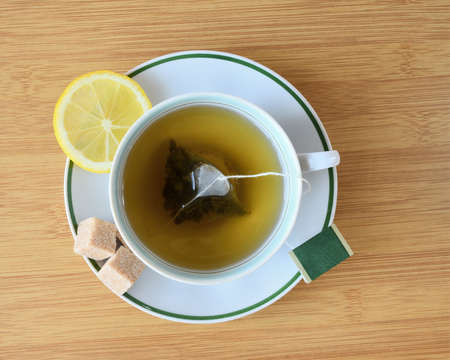 Cup of green tea with slices of lemon and pieces of sugar top view on the table.