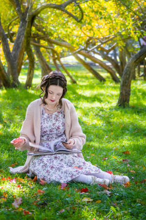 Happy girl is sitting under a tree and reading book on a beautiful autumn day.