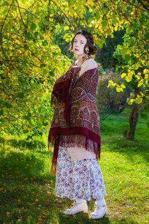 Sad women in a shawl in the park on an autumn day