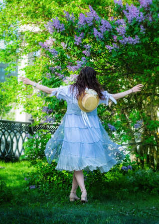 Young beautiful girl is spinning in a dance in a park rejoicing on a warm sunny day.