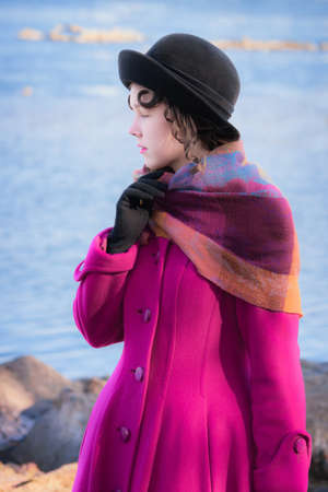 Portrait girl in a bright crimson coat and a black hat against the background of the sea landscape looks into the distance