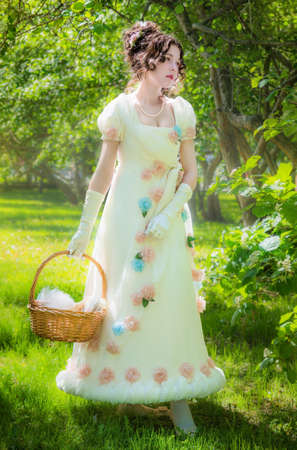 Beautiful woman in an historical bride dress with a wicker basket in her hands in a spring garden for a walk.