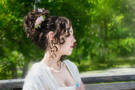 Portrait of a beautiful woman in a white dress with a hairstyle of bride in spring garden.