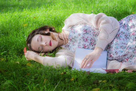 A girl with a book fell sleep in the park on grass on a warm autumn day.