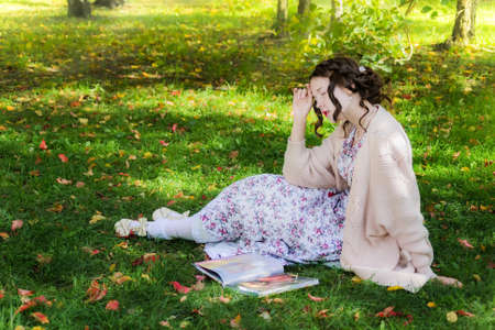 Tired woman is sitting under a tree and reading book on a beautiful autumn day.