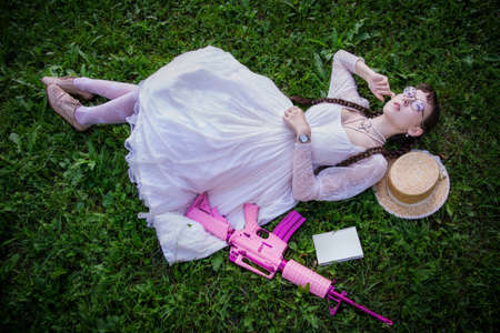 Woman with a dreamy look with a book and a pink rifle lies on grass, top view.