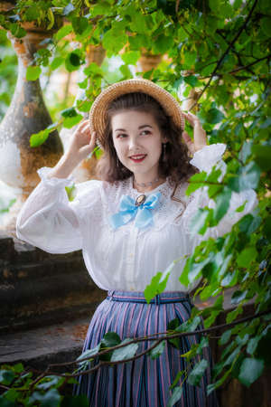 Portrait happy girl in a vintage clothes and a straw hat near a tree on a summer day.