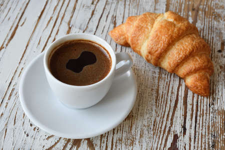 Ð¡up of coffee and croissant on a wooden table top view. Stock Photo