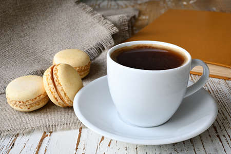 Still life with a cup of coffee, makroons and a book on the table. Stock Photo