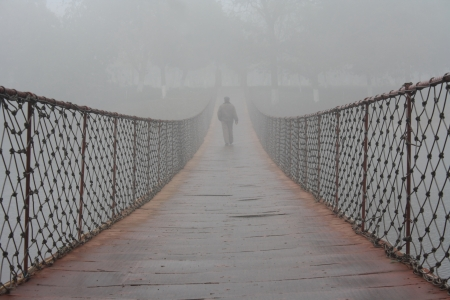In the fog, a man walking on the bridge photo