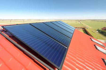 cobradores: Detalle de paneles solares en rojo crea un mosaico con techo y hermoso cielo azul.