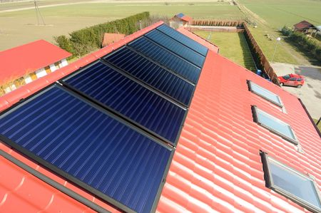 energy sources: Close up of red roof with solar panels. Green field  in background.