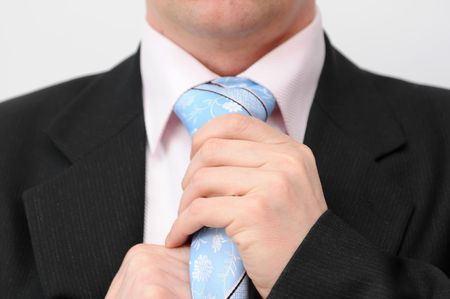Closeup of businessman doing a blue tie. Isolated on a white background. photo