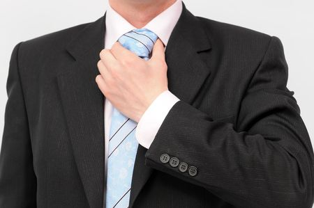 Closeup of businessman doing a blue striped tie. Isolated on a white background. photo