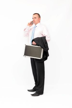 Young standing businessman with a briefcase, talking by mobile phone. Isolated on a white background. photo