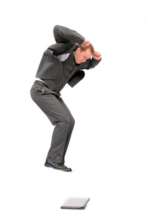 destroying: Crazy businessman jumping on his portable computer. Isolated on the white background. Stock Photo