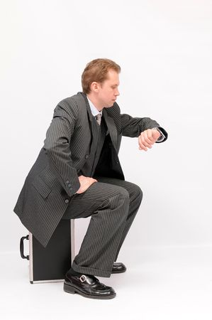 Young businessman seating on a briefcase and looking at a watch. Isolated on a white background. photo
