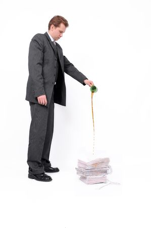 Downhearted businessman pouring coffee from a cup on a heap of documents isolated on a white background. photo